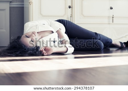 Sad beautiful fashion woman lying on the floor at apartment - stock photo