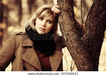 Sad beautiful fashion woman walking in autumn forest - stock photo