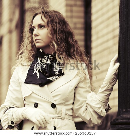 Sad beautiful fashion woman with long curly hairs in white coat - stock photo