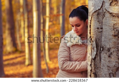 Sad beautiful woman in forest while autumn season - stock photo