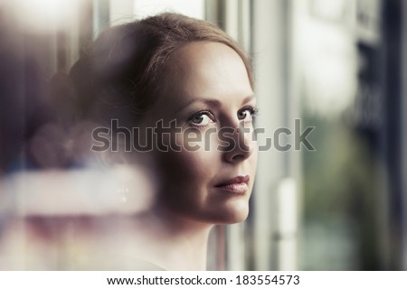 Sad beautiful woman looking out window  - stock photo