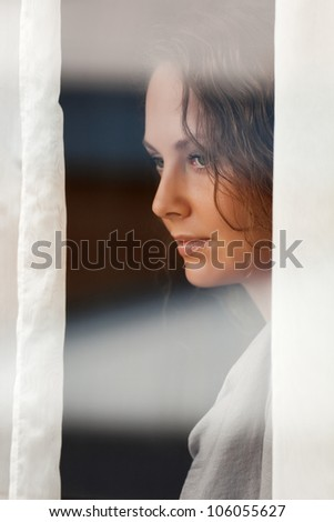 Sad beautiful woman looking through the window - stock photo