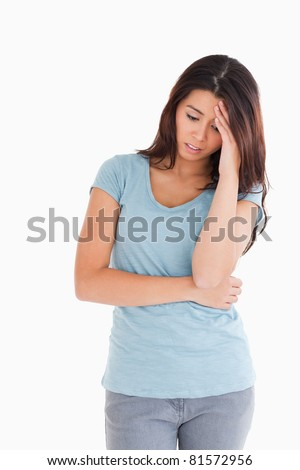 Sad beautiful woman standing against a white background - stock photo