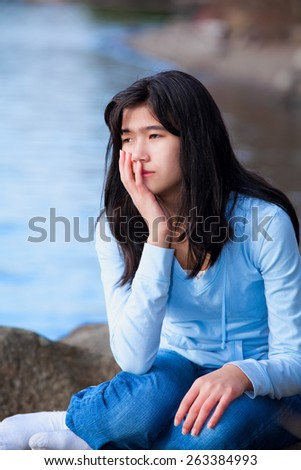 Sad biracial teen girl in blue shirt and jeans sitting on rocks along lake shore, lonely expression - stock photo