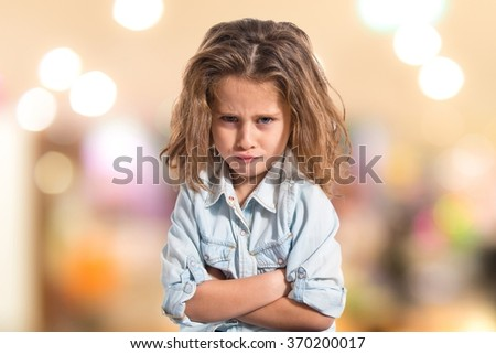 Sad blond baby girl on unfocused background - stock photo