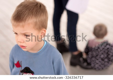 sad blond boy jealous about being neglected by his mother or caregiver who is giving attention to another child - stock photo