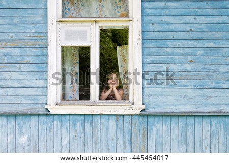 Sad bored little girl looking out the country house window leaning her face on her hands. Outside view - stock photo