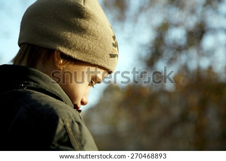 Sad boy in autumn warm clothes outdoors - stock photo