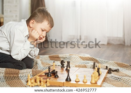 sad boy lost a game of chess sitting in front of a chessboard - stock photo