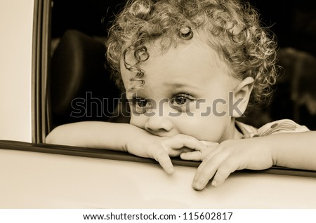 sad boy near car window - stock photo