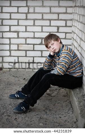 sad boy on background wall - stock photo