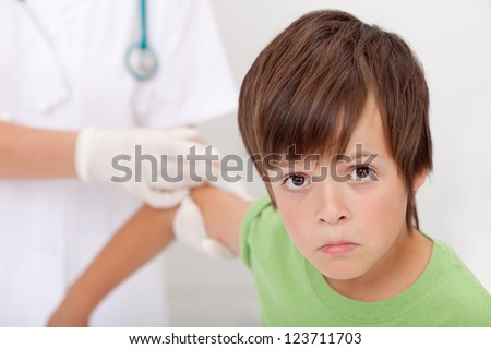 Sad boy receiving injection - health-care and vaccines concept - stock photo