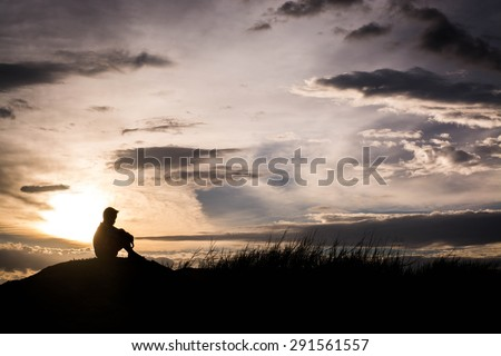 Sad boy silhouette worried on the meadow at sunset ,Silhouette concept - stock photo