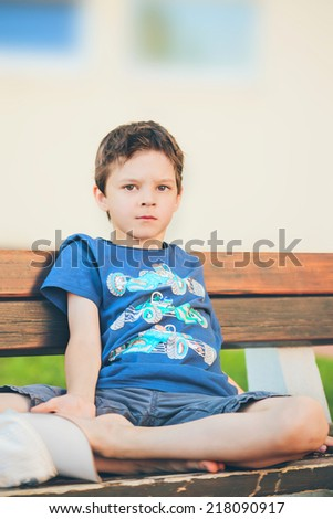 sad boy sitting on a bench and looking into the camera - stock photo
