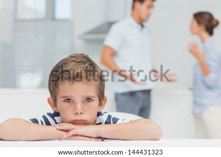 Sad boy with arms folded while parents quarreling in the kitchen - stock photo