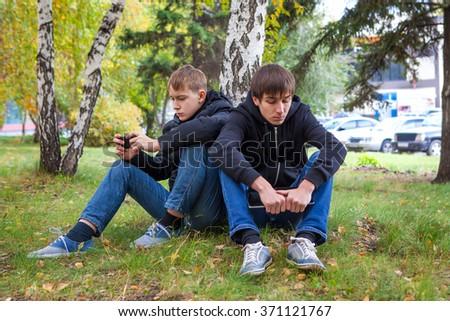 Sad Boys sit under Tree in the Autumn Park - stock photo