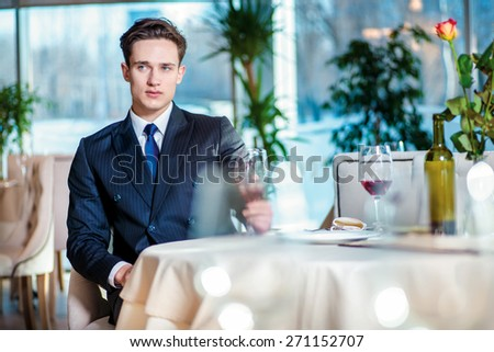 Sad businessman. Confident businessman in formal wear sitting at a table in a restaurant while holding a glass of wine and looking ahead - stock photo