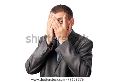 sad businessman covering face by hands and looking through fingers isolated on white background - stock photo