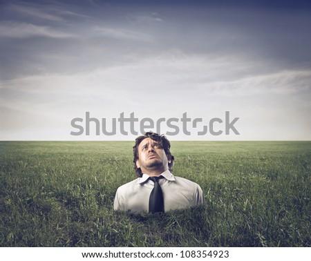 Sad businessman half-buried in a green meadow - stock photo