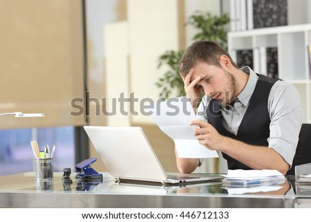 Sad businessman reading bad news in a letter sitting in a desk at office - stock photo