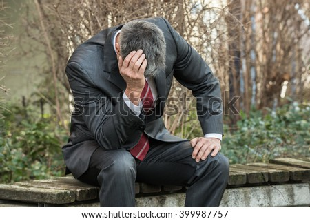 Sad Businessman Sitting On The Bench Outdoors And Having Headache - stock photo
