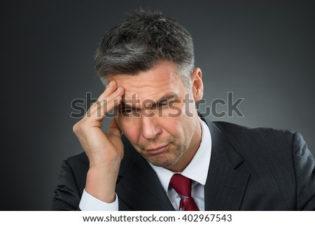 Sad Businessman Suffering From Headache Over Black Background - stock photo