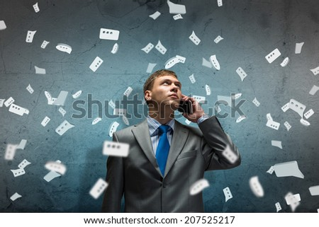 sad businessman talking on a cell phone with tears in his eyes - stock photo