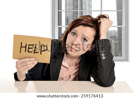 sad businesswoman in stress at office work asking for help sitting frustrated and depressed in front of business district window view pulling her red hair - stock photo