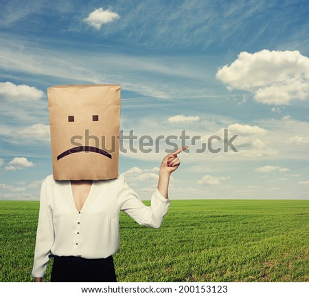 sad businesswoman pointing at something over green field - stock photo