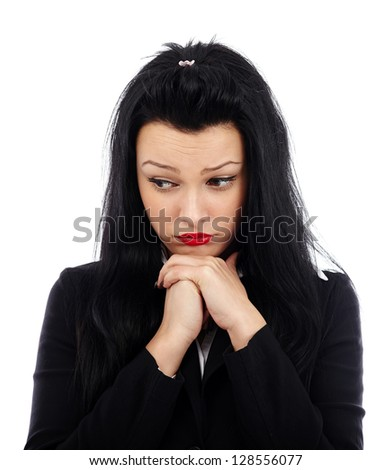 Sad businesswoman with her hands at her chin, looking down, isolated on white background - stock photo