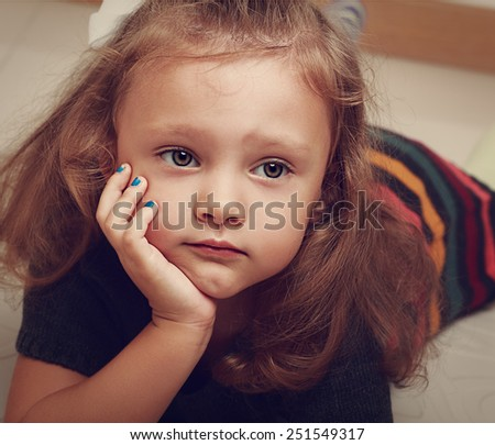 Sad child girl thinking about. Closeup vintage portrait - stock photo