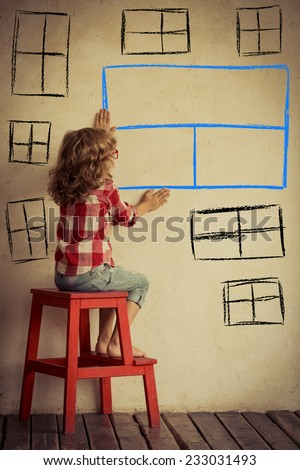Sad child sitting against old wall with drawn window. Freedom and imagination concept - stock photo