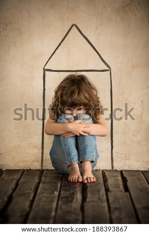 Sad child sitting on the floor. Homeless kid in dark room - stock photo