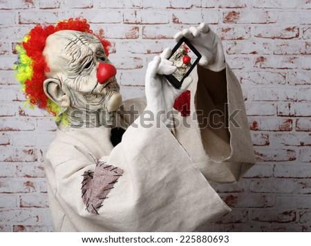 Sad clown makes selfie on cellphone. Halloween Costume. - stock photo