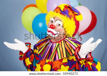 Sad clown throws up his hands in despair.  Contrast between the fun costume and unhappy expression. - stock photo