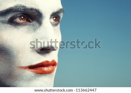 Sad clown with makeup on a blue background - stock photo