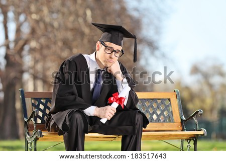 Sad college student sitting on a bench in park  - stock photo