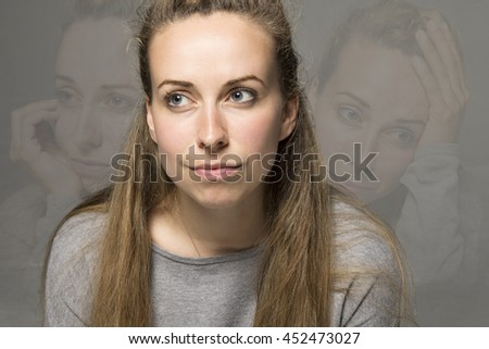 Sad concept young woman with wry smile but hiding tears and sadness in images behind  - stock photo
