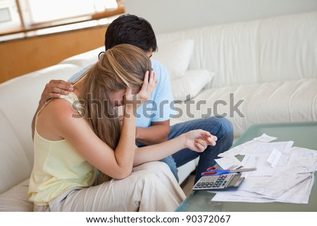 Sad couple in financial trouble in their living room - stock photo