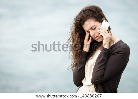 Sad crying woman talking on the phone. Emotional crisis, troubles and love depression concept. - stock photo