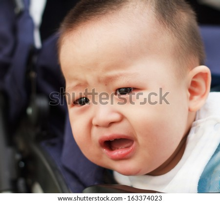 sad cute asian baby watching out from baby car - stock photo