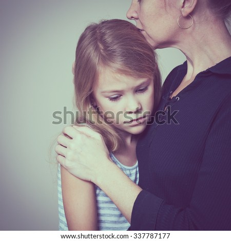 sad daughter hugging his mother at home. Concept of couple family is in sorrow. - stock photo