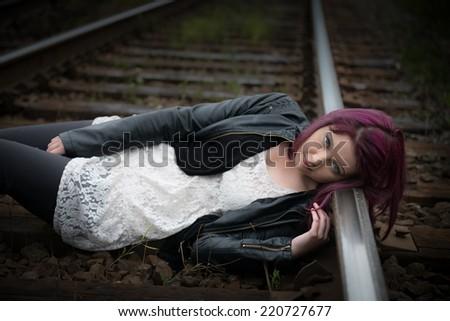 Sad, depressed teen girl lies on railway tracks - stock photo