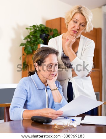 Sad elderly ladies checking invoices at office.Focus on the left woman - stock photo