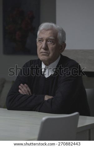 Sad elderly lonely man sitting at home - stock photo