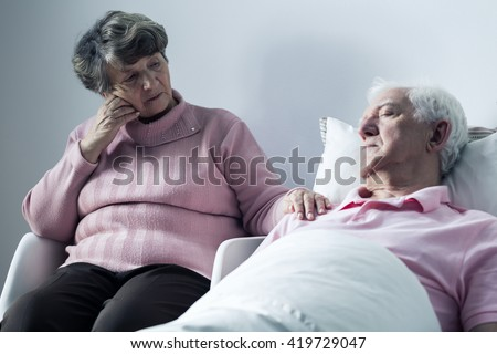 Sad elderly woman and her sick husband lying in a hospital bed - stock photo