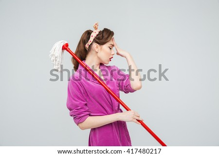 Sad exhausted young housewife with mop having a headache  - stock photo