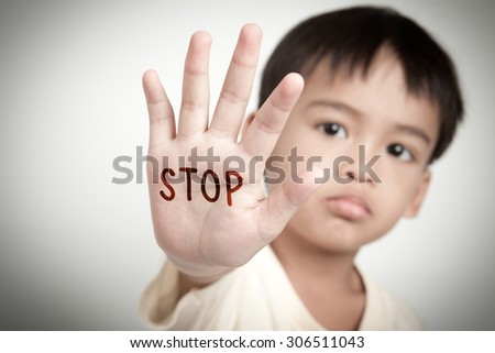 sad face of asian kid and hand raise stop written on his hand. - stock photo