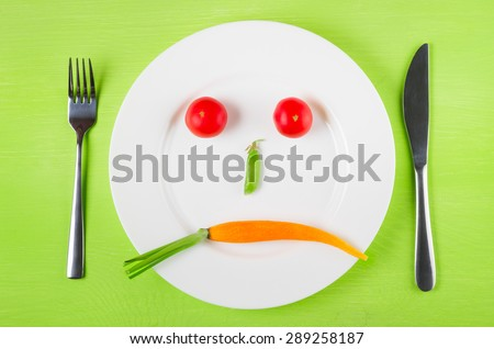 Sad face of vegetables, the concept of dietary restrictions, healthy lifestyle, diet,  weight loss, anti-obesity, healthy diet. Two tomatoes, peas in a pod and carrots on a plate, knife, fork - stock photo