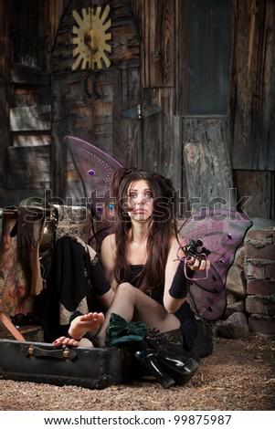 Sad Faery sitting in suitcase holding Jeweler glasses - stock photo